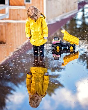 plymouth, ma child photographer | heidi harting | young boy in yellow raincoat with yellow truck reflected in puddle