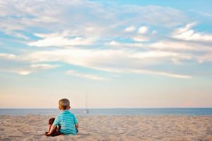 Boy and his stuffed animal atthe beach with sailboat in the distance by plymouth ma child photographer Heidi Harting