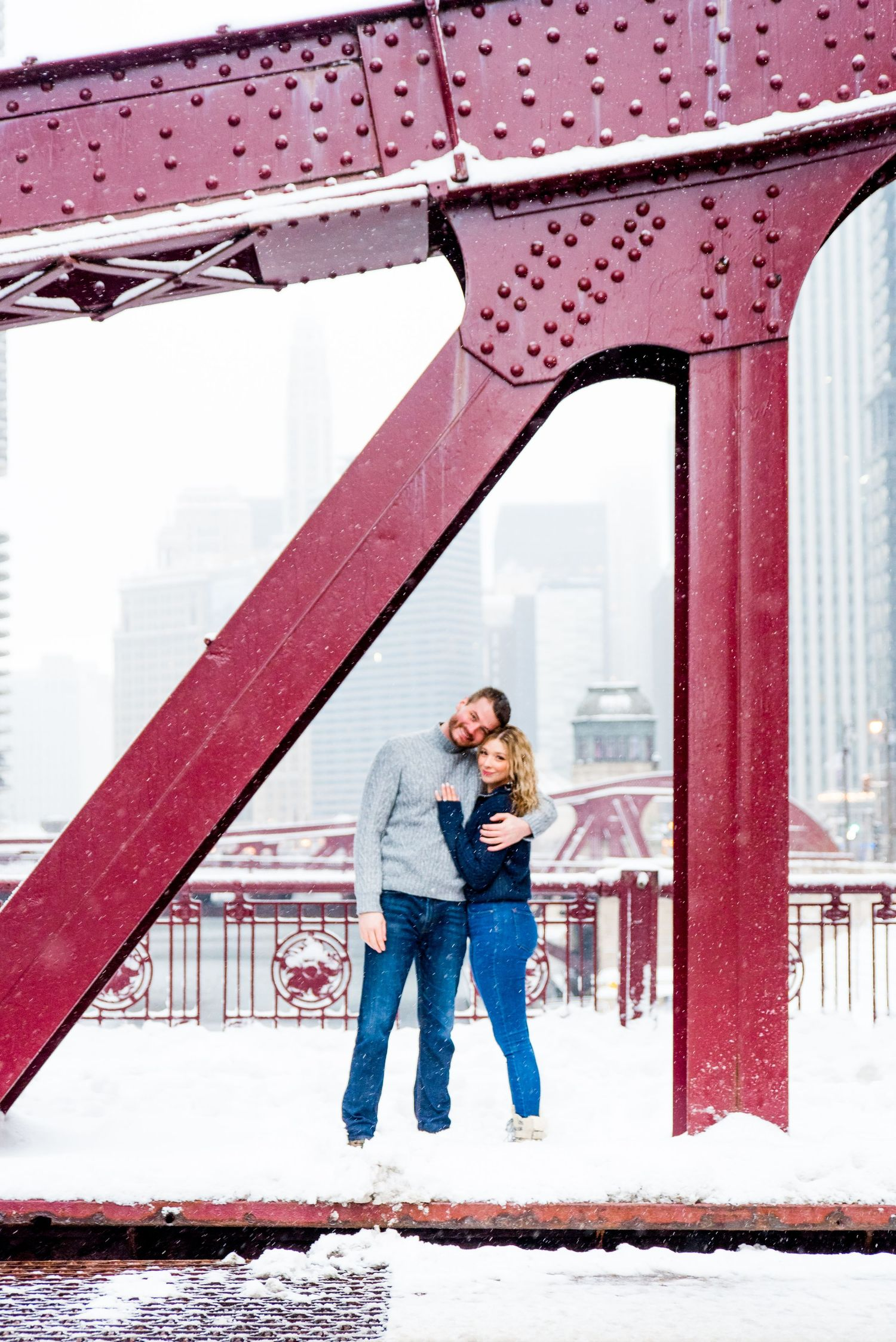 young couple hugging under bridge for Chicago urban engagement pictures in the snow