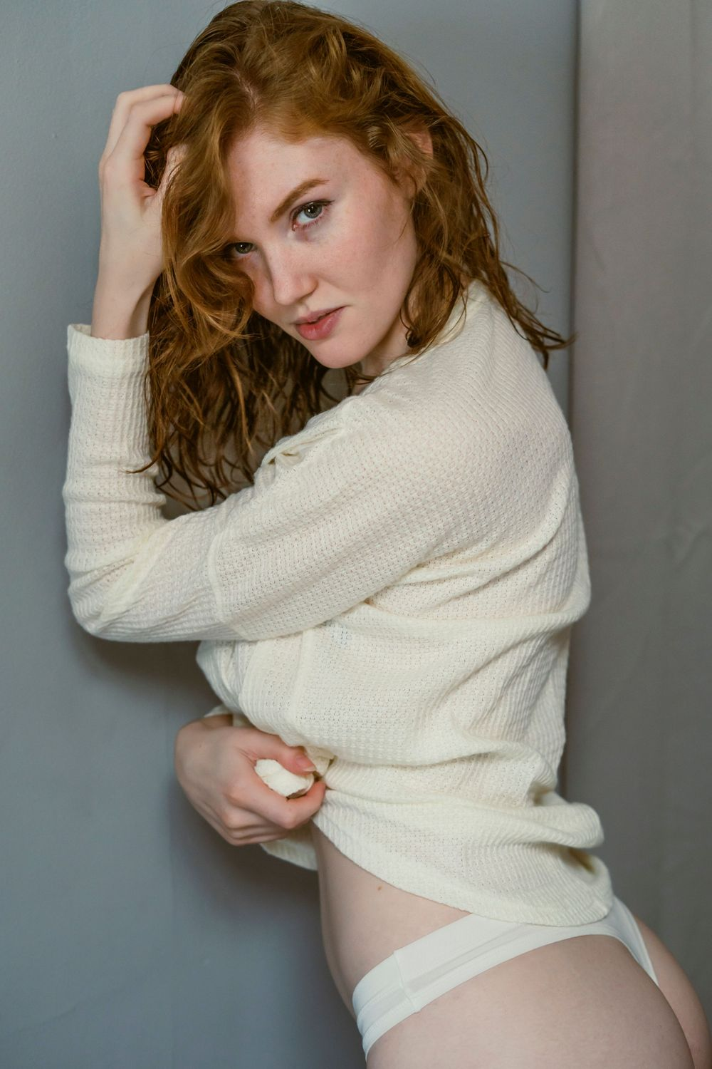 A slender woman with red hair leaning against a wall with one hand in her hair and the other grabbing her sweater