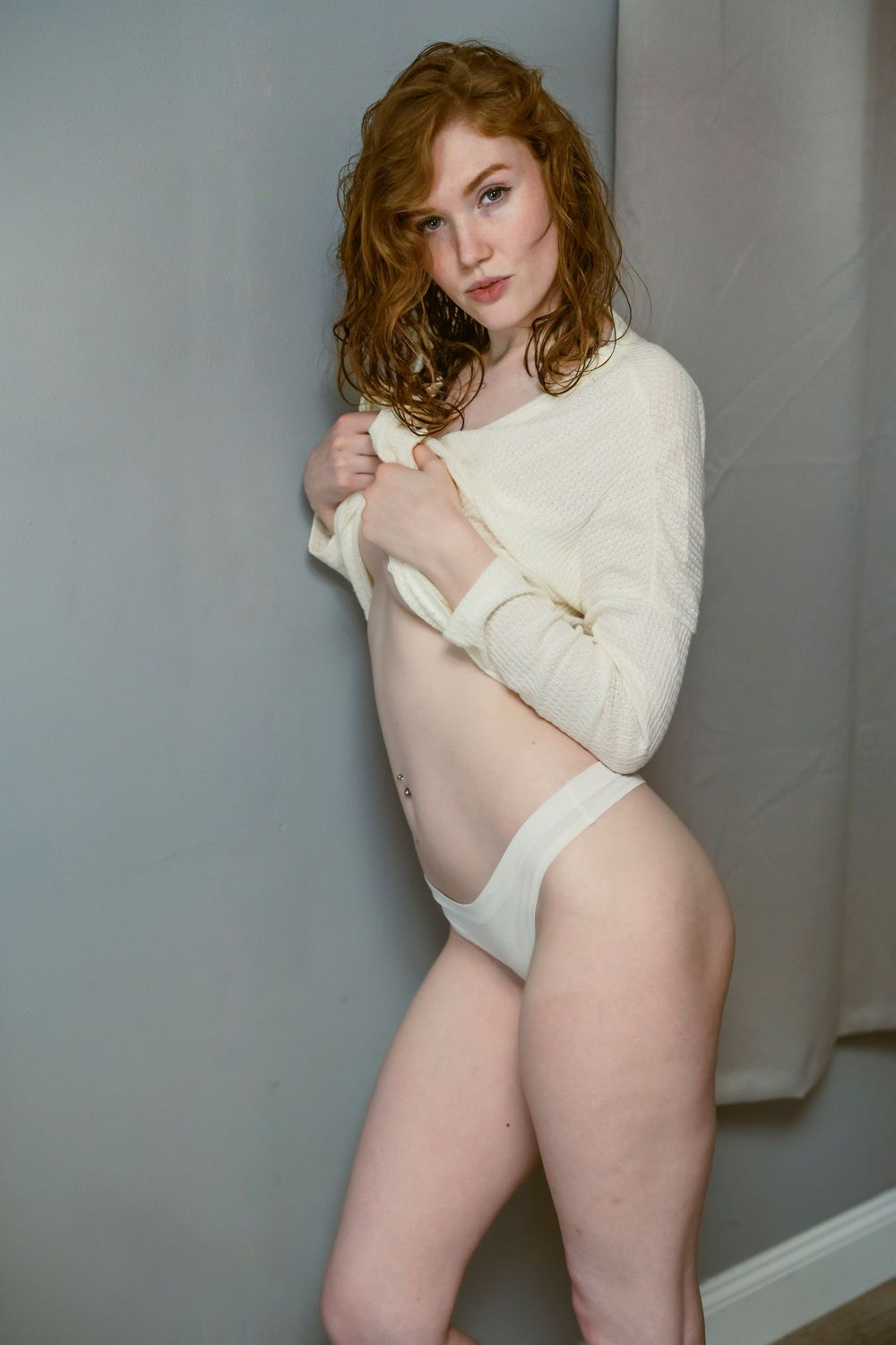 A woman with red hair in a white sweater and white panties lifting the sweater up to her chest and exposing her stomach