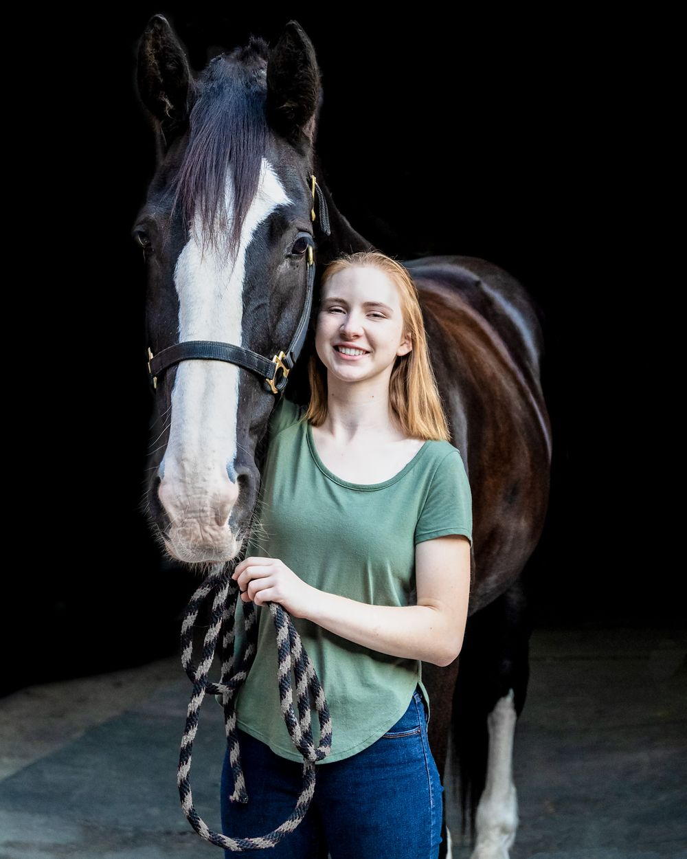 A young girl standing with a dark horse in front of a black background