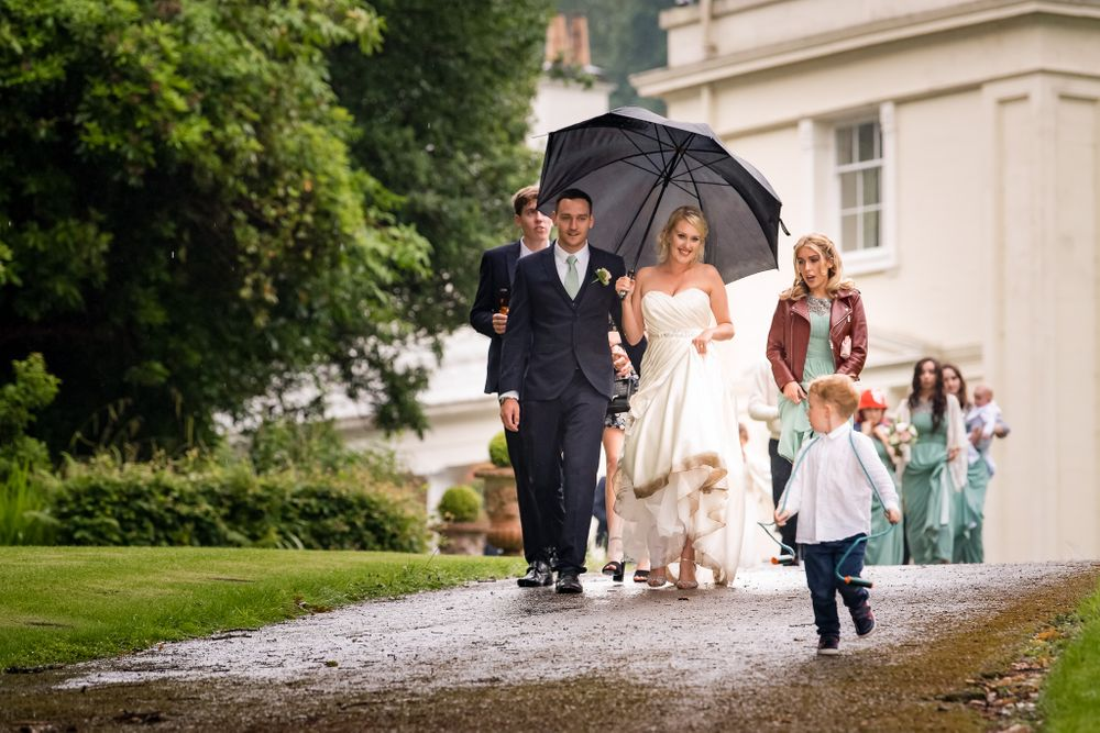 Wedding party under umbrella at Storrs Hall in Lake District