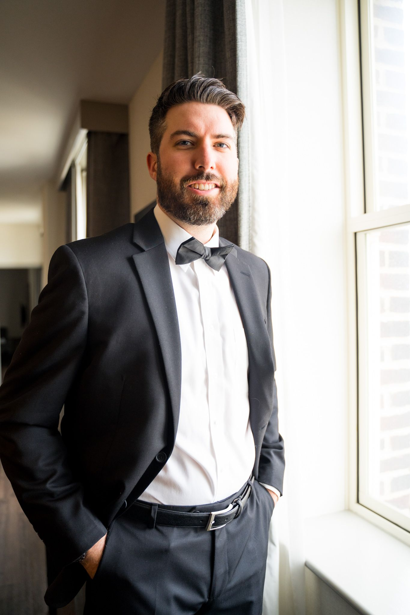 brunette groom with beard in black suit and bowtie smiling next to window in for downtown St. Louis wedding