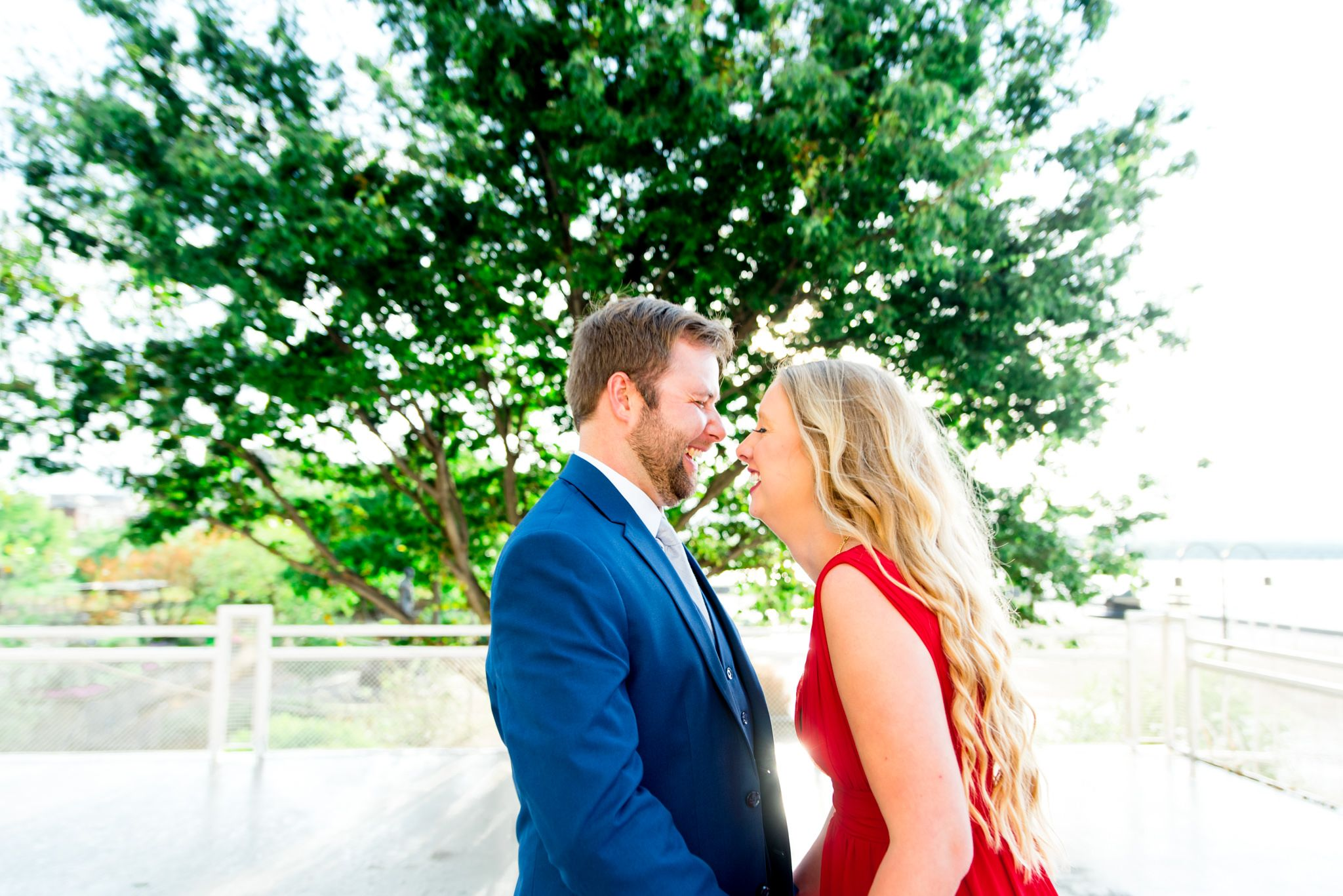 blonde woman in red dress and man in navy suit laugh with each other with eyes closed in front of big tree