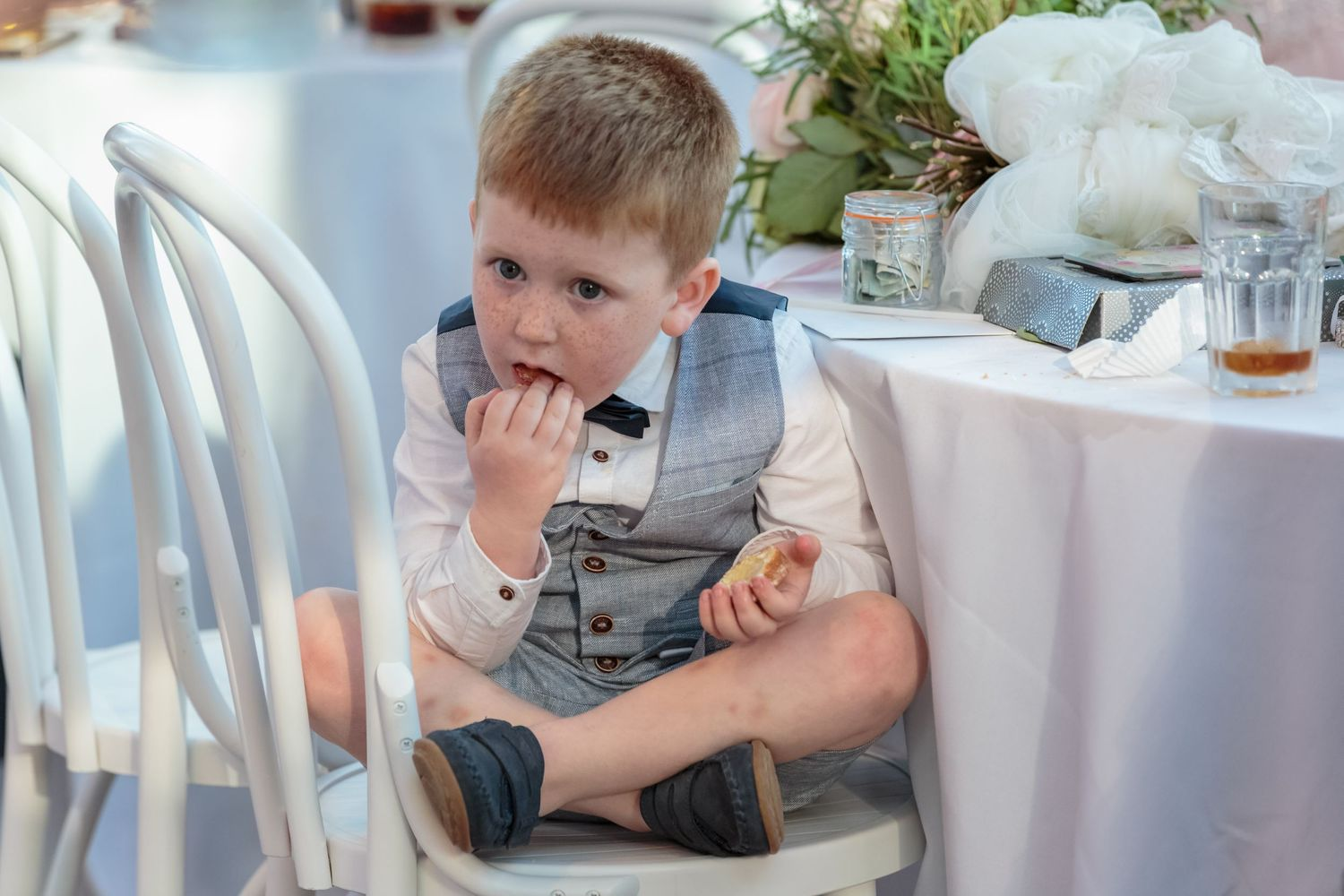bride and grooms son sits cross legged on a chair eating a cake in siren liverpool