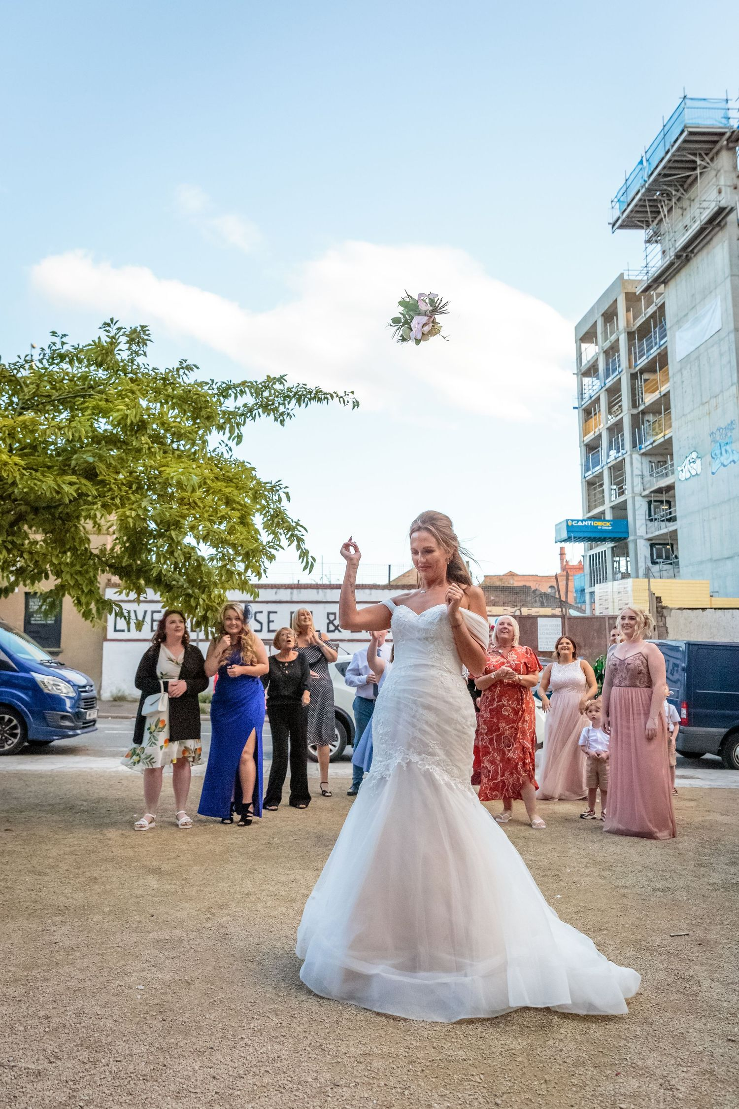 brides bouquet in the air as she throws it over her head for one lucky lady to catch
