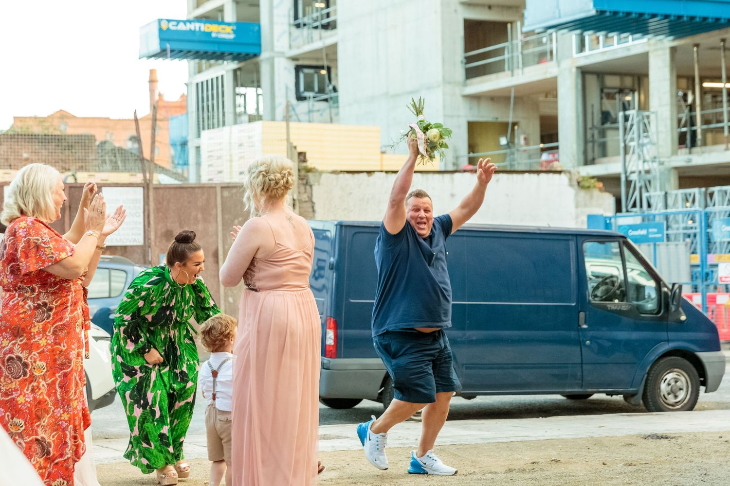 a man in shorts and t shirt at the back appears from nowhere to catch the bouquet arms in the air to celebrate