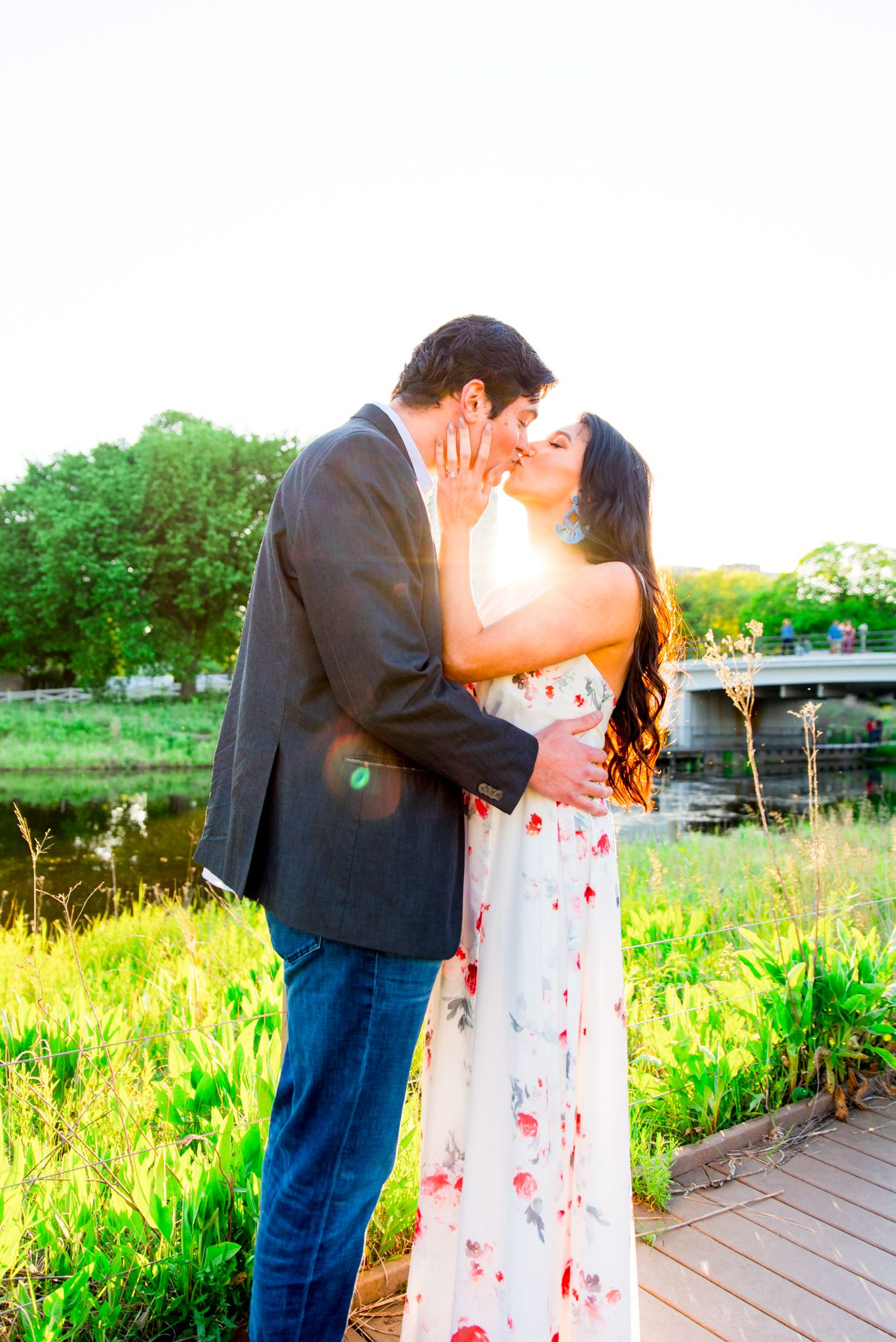 man in suit and woman in floral maxi dress kissing at sunset in Lincoln Park for engagement pictures