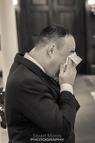 crying groom uses a handkerchief to wipe tears away from his eyes  during the wedding ceremony