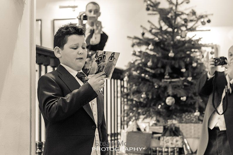 the couples son gives a reading during the ceremony a christmas tree in the background behind him