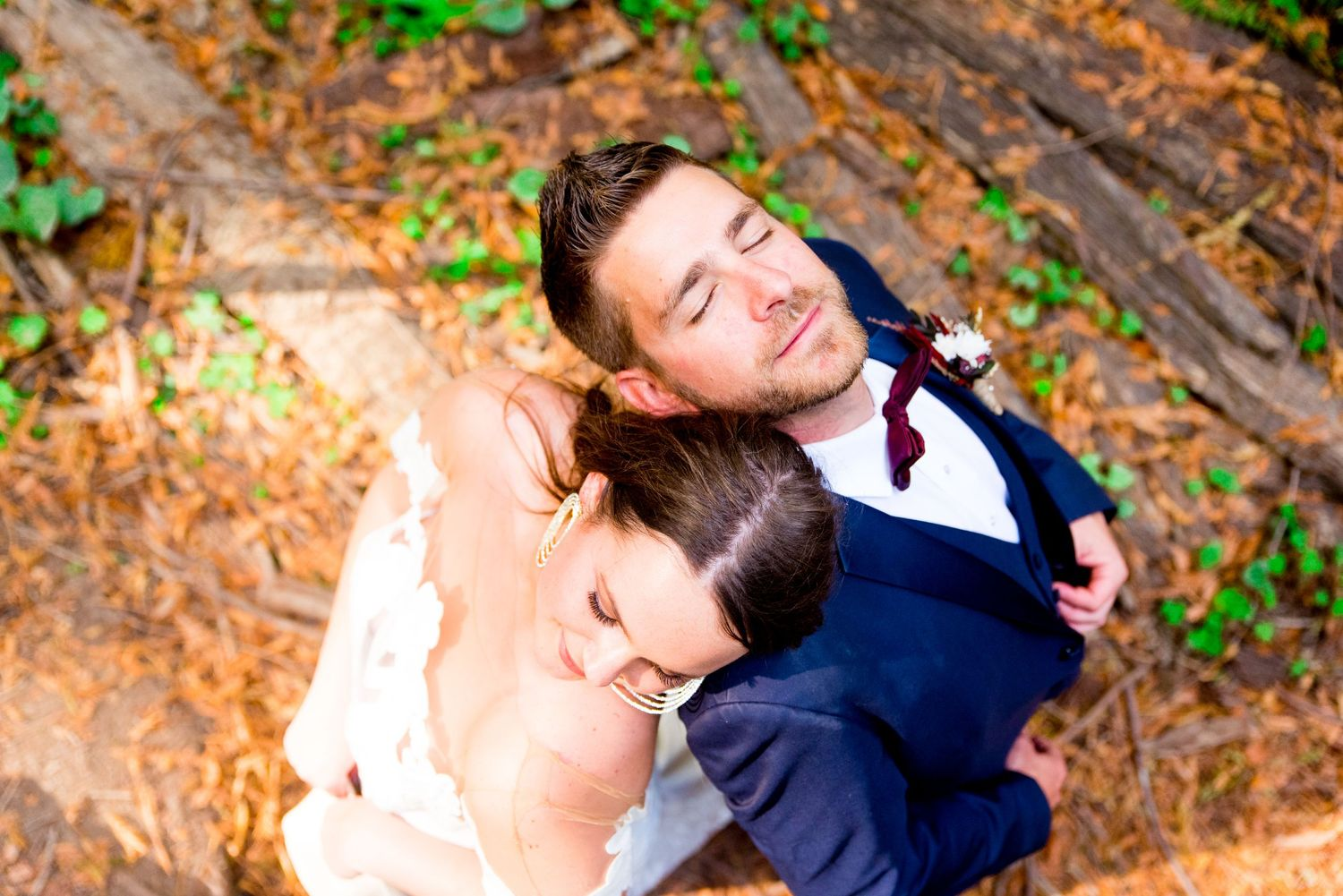 bride and groom lay heads on each other with eyes closed in the Northern California Redwoods on wedding day