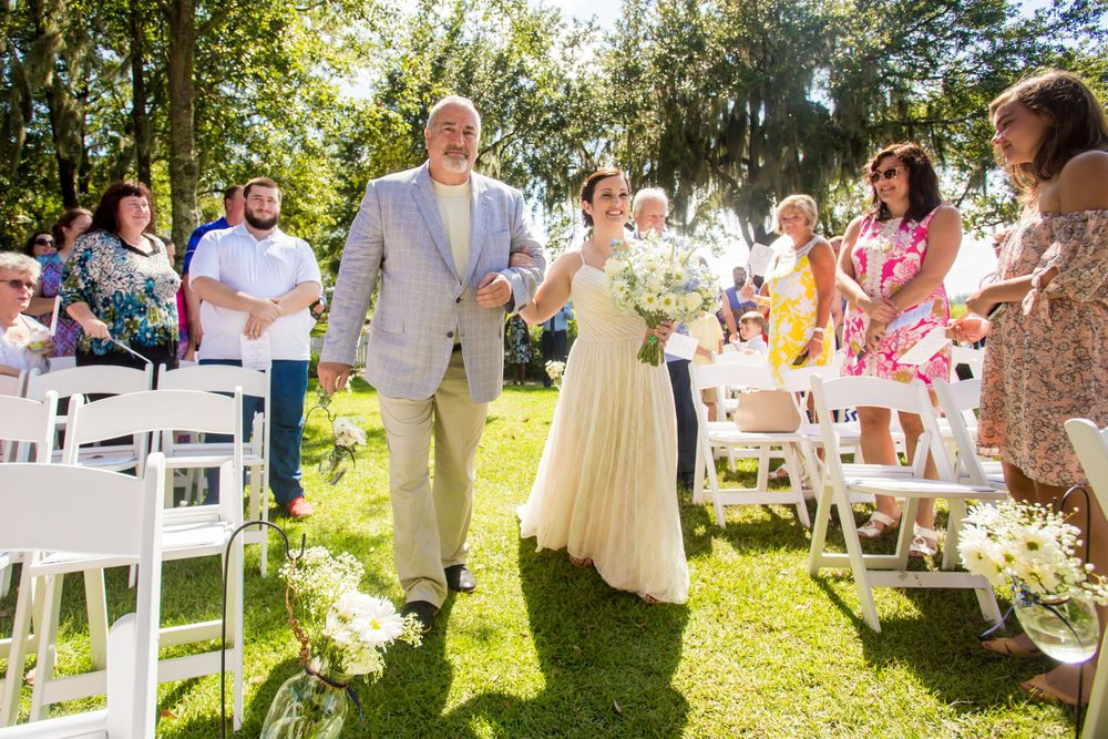 Bride Clare is walked down the aisle by her father during her wedding ceremony at I'On Club in Mt. Pleasant, SC