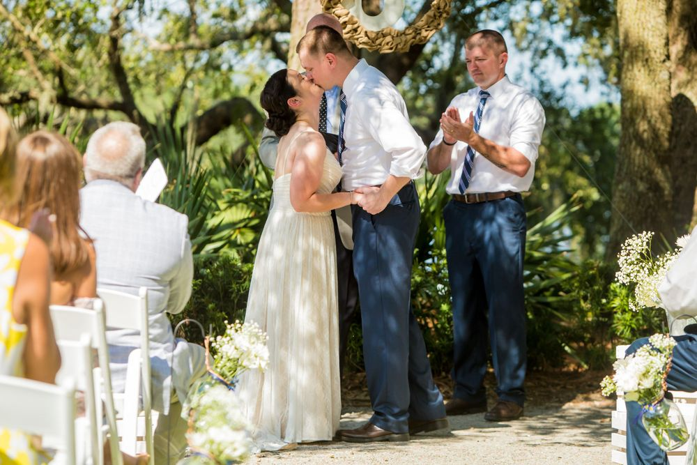 Bride Clare and groom Curtis have their first kiss during their wedding ceremony at I'On Club in Mt. Pleasant, SC