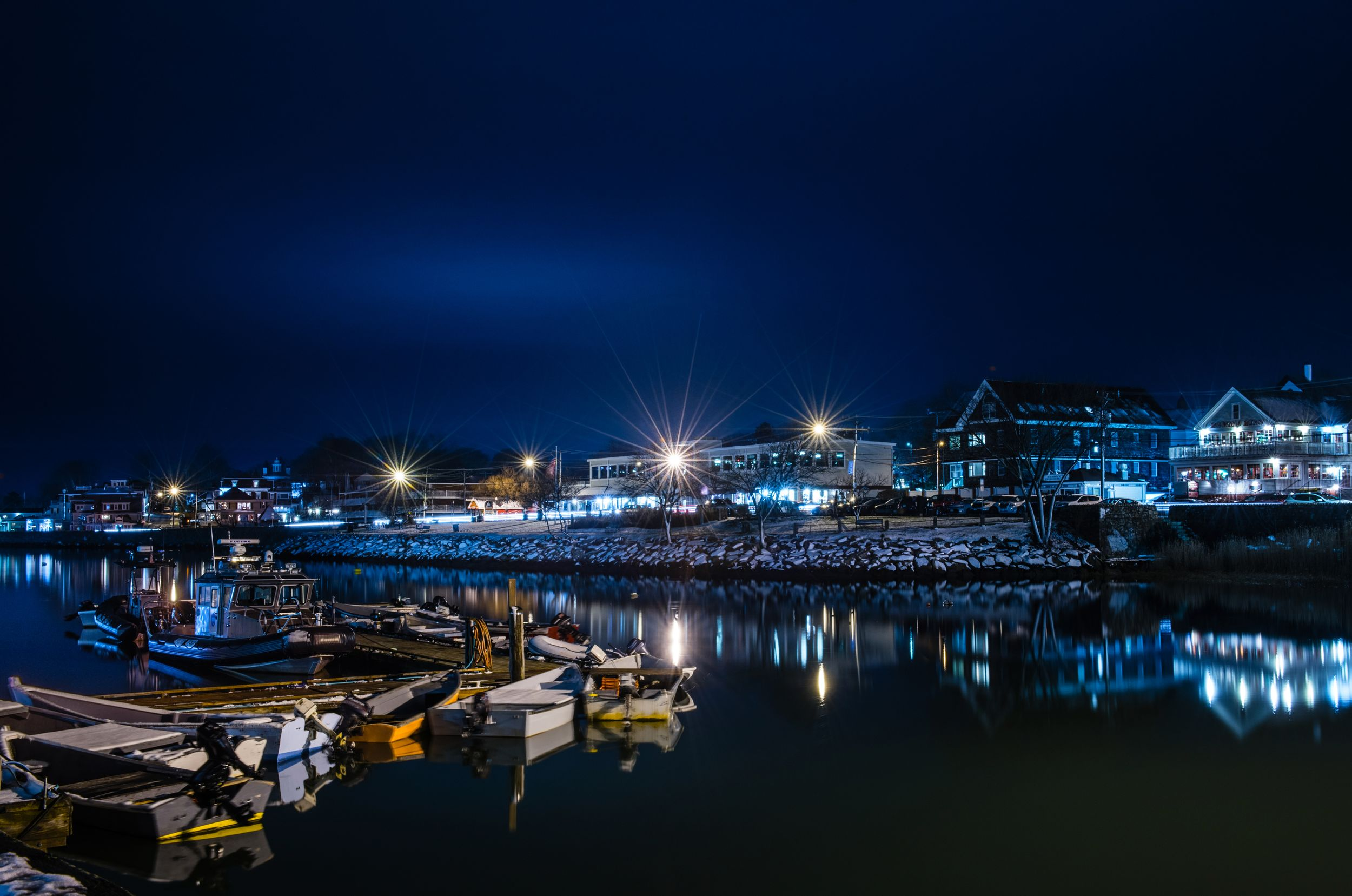 Night view of Plymouth Waterfront, looking at  Water Street. Boats and businesses in the image.