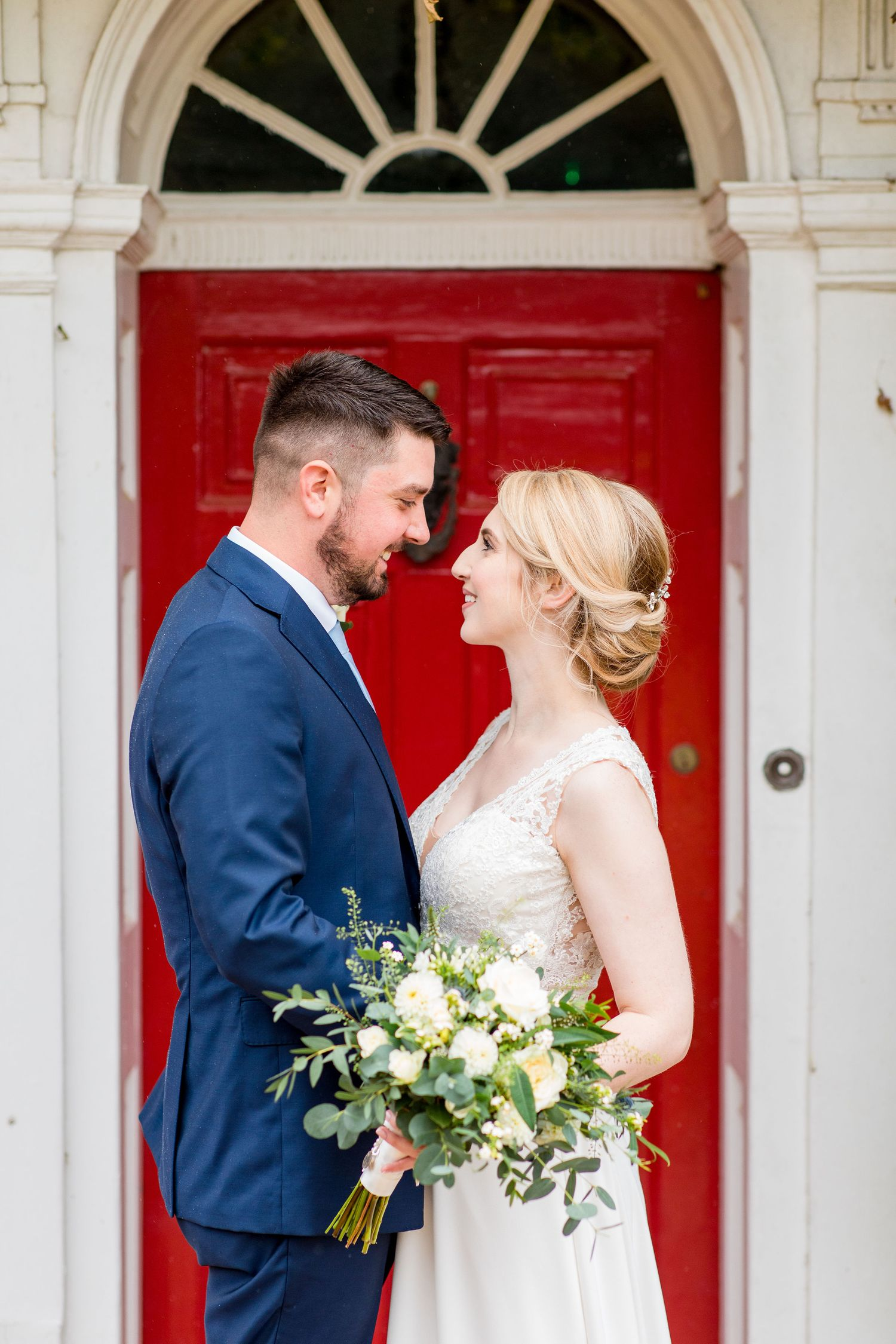 Bride and Groom cuddle infront of red door for wedding photography