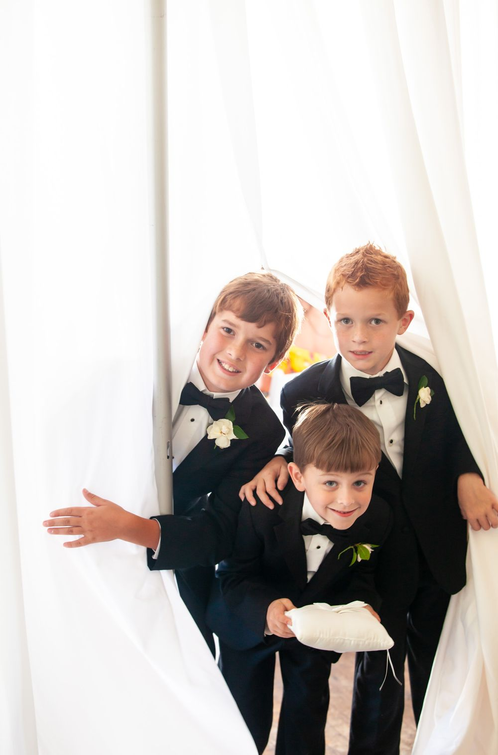 Ring bearers peak out from behind a curtain before a wedding at the SC State Museum in Columbia, SC.