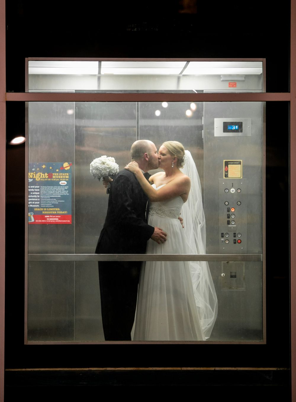 Maggie and Bryan kiss in the elevator following their wedding at the SC State Museum in Columbia, SC.