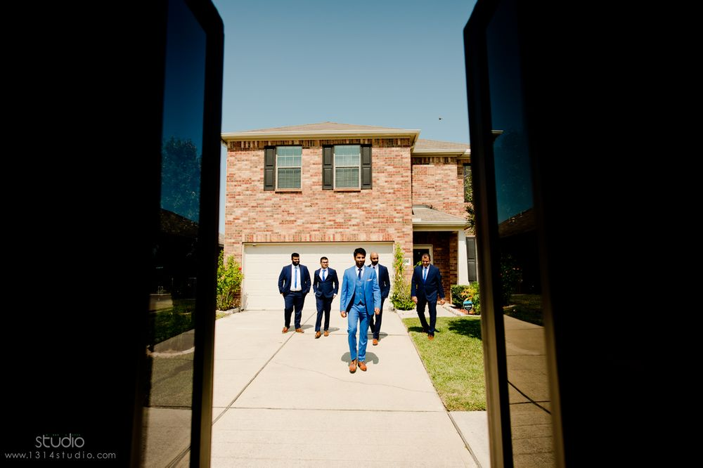 groom and groomsmen walking to the limo