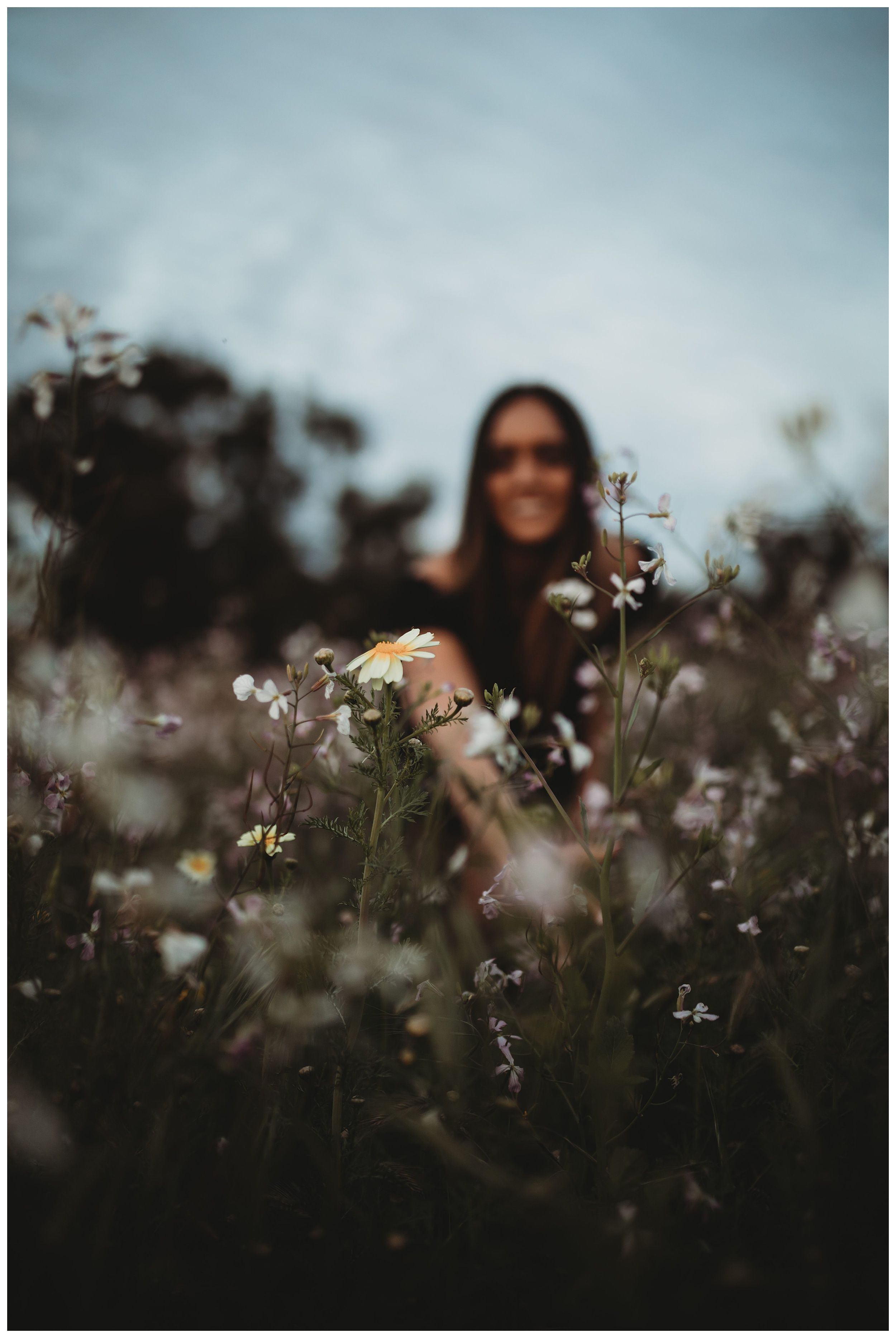 girl looking at flowers in flower field
