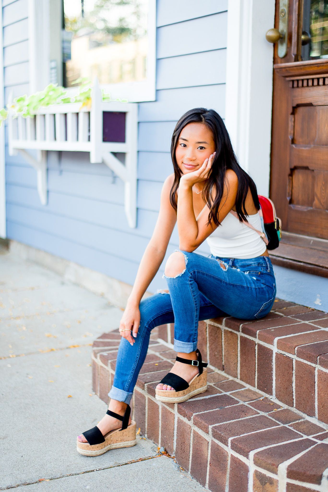 high school senior girl sitting on a stoop smiling with hand on face