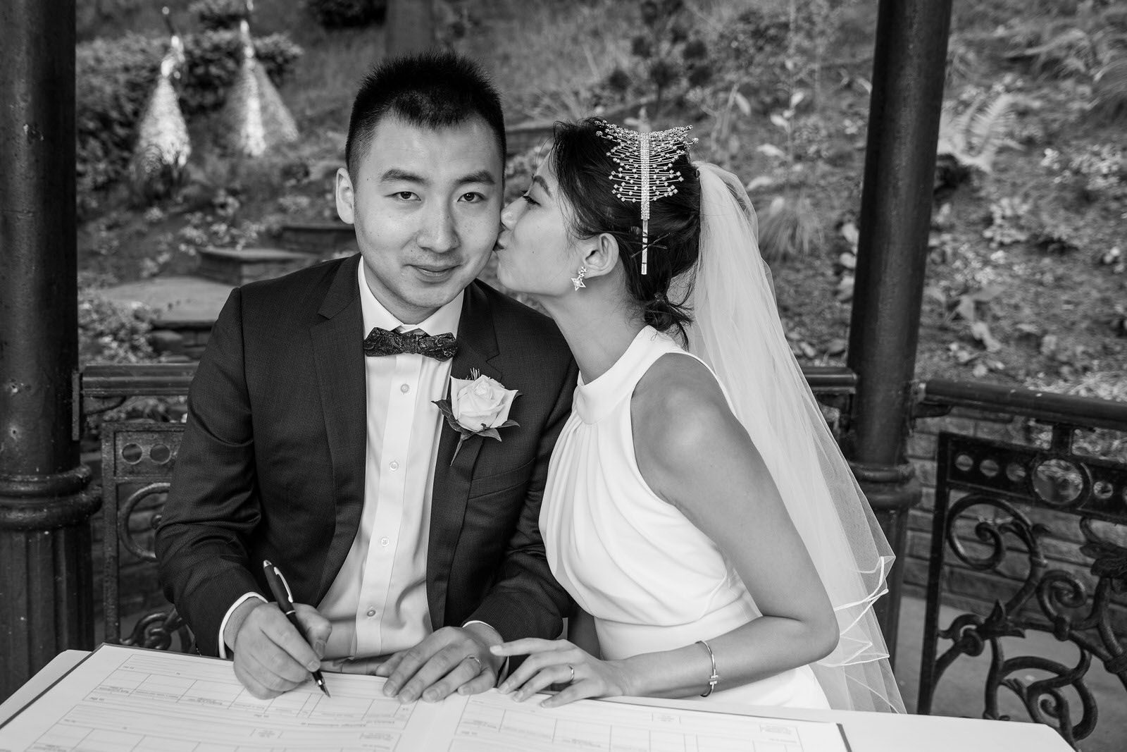 Chinese Bride & Groom kissing whilst signing wedding register