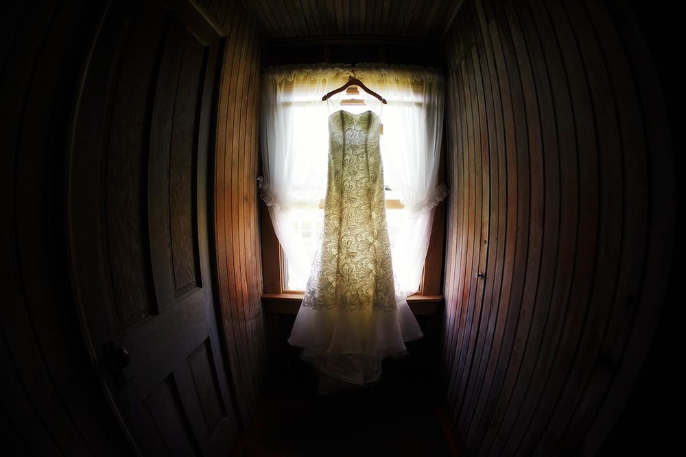Wedding dress hanging in a window during a wedding day in Massachusetts