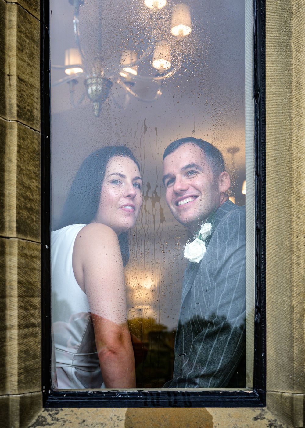 Bride and groom looking out window on rainy day at Cragwood