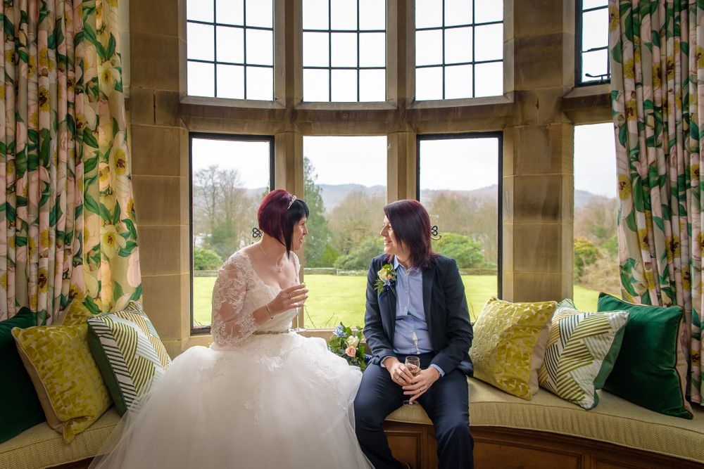 Two brides sitting in bay window at Cragwood Country House Hotel