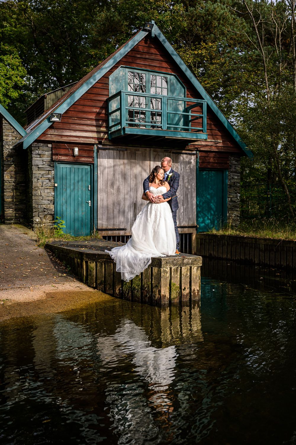 Bride and groom gazing out over Windermere at Cragwood boathouse