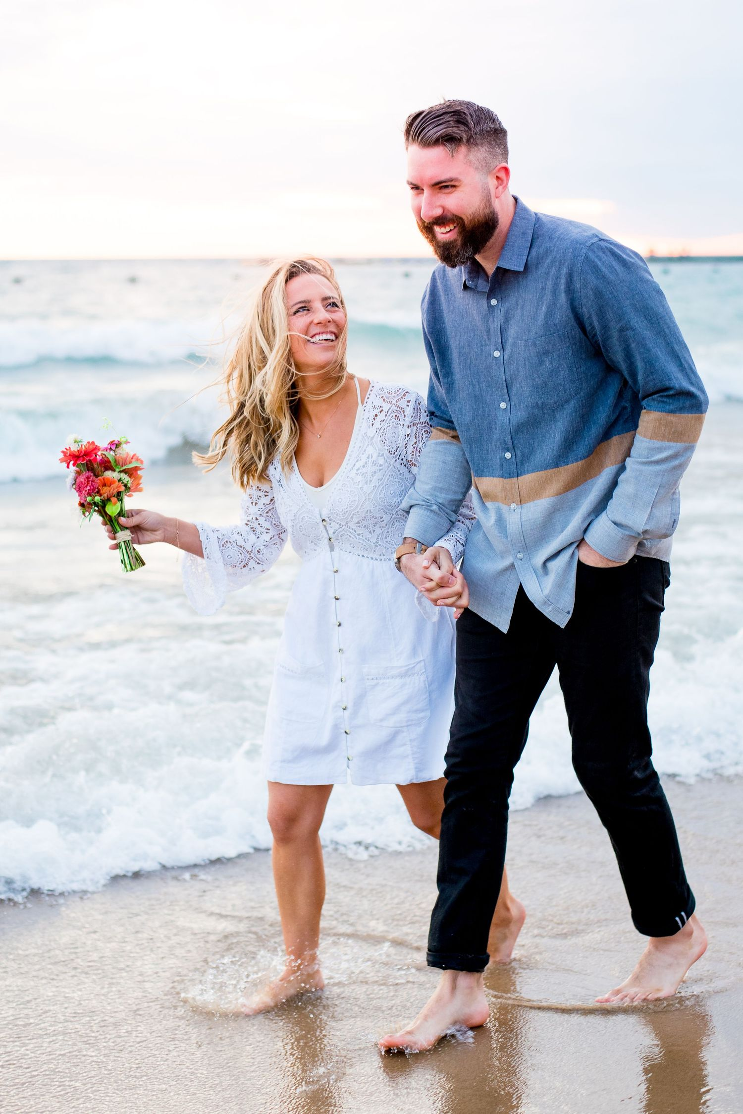 blonde woman in white dress looks at her fiance as they walk along North Avenue Beach Chicago and laugh at sunrise