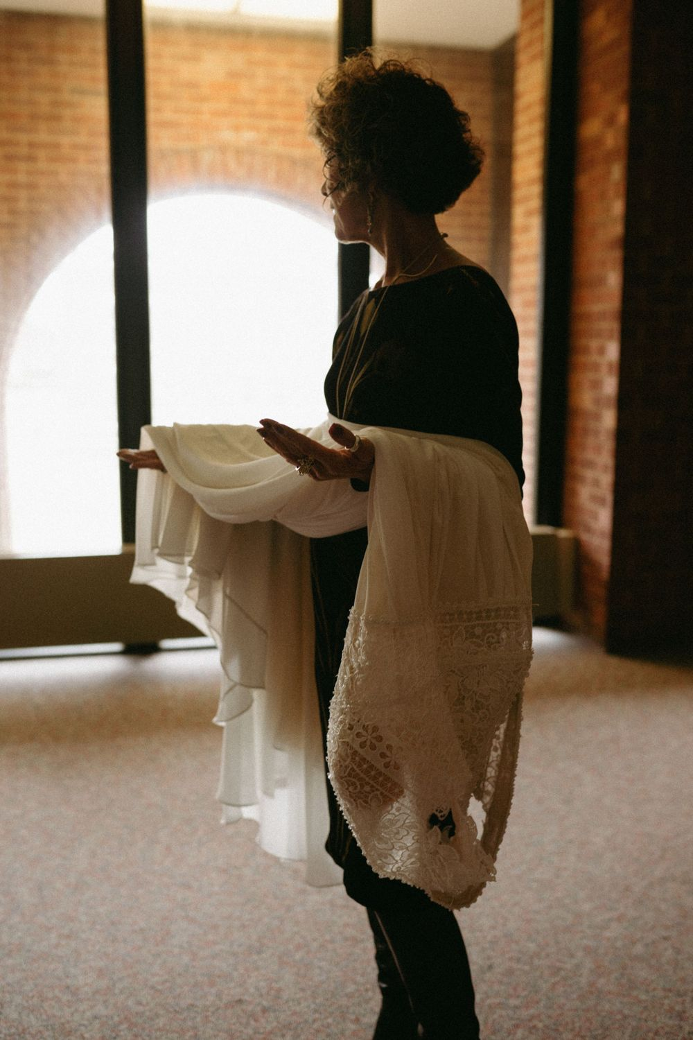 mother-of-bride-holding-dress-wedding-cowles-library-desmoines-iowa-raelyn-ramey-photography