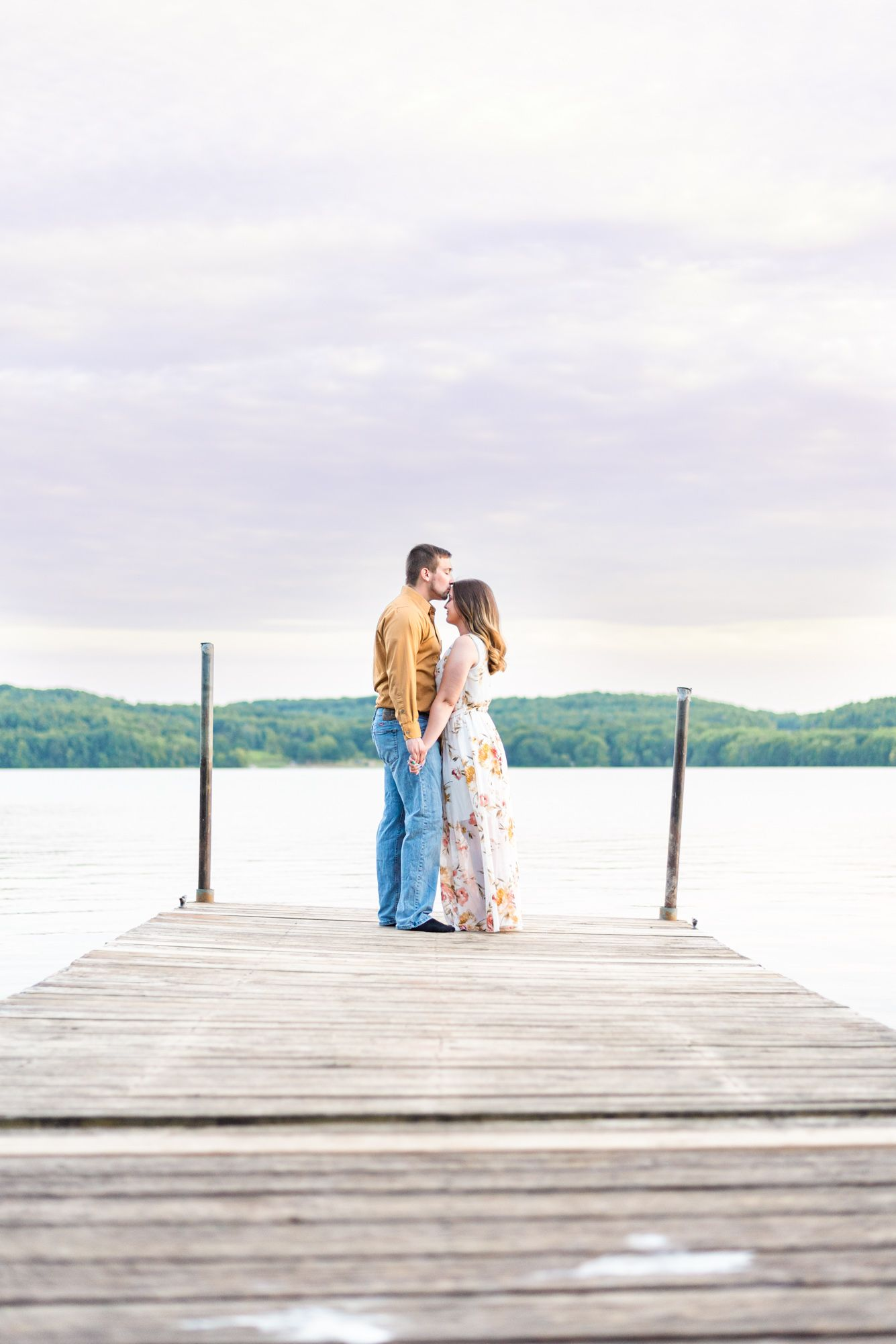Couple kissing on dock of Lake Arthur at Moraine State Park in Pennsylvania