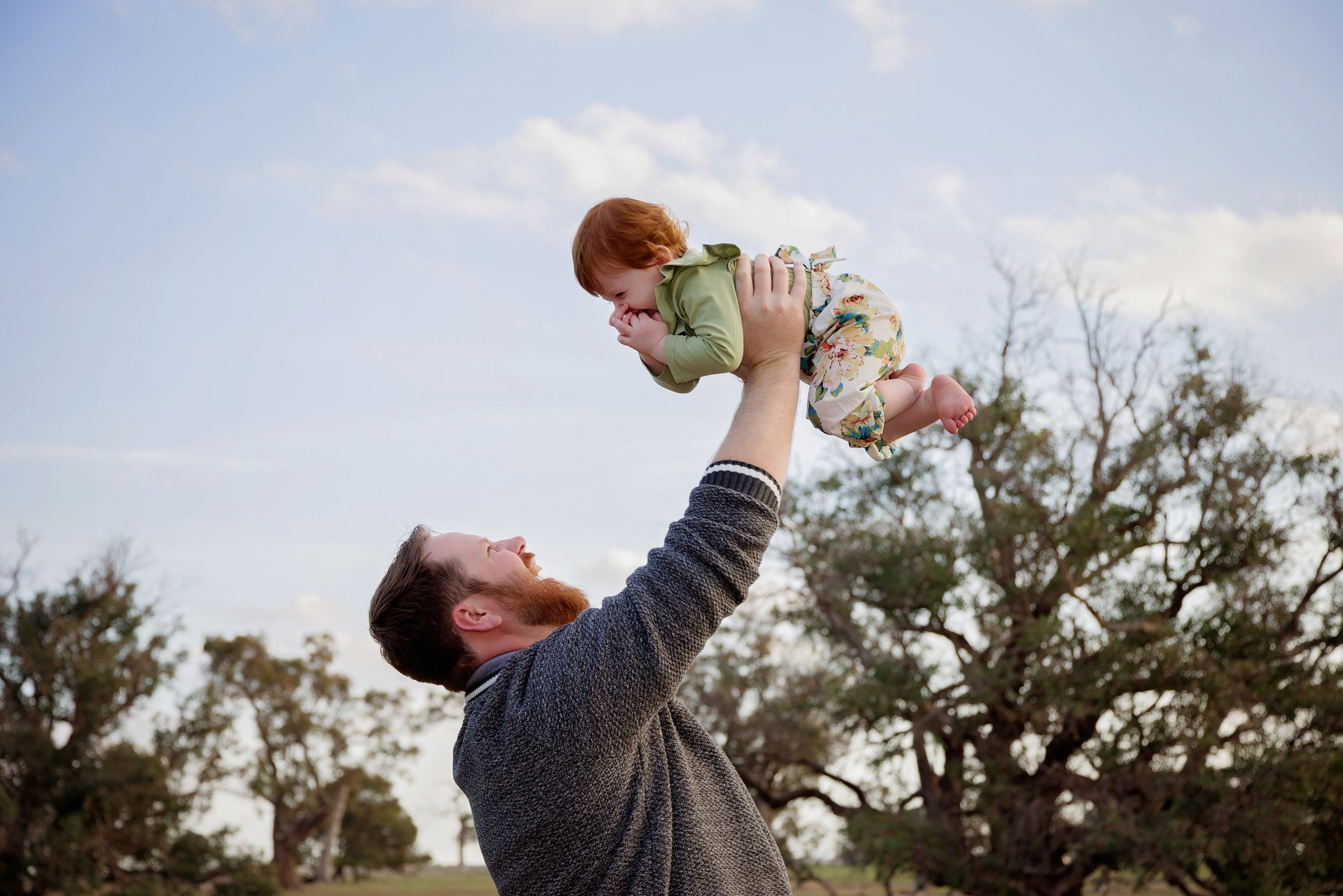 father holding baby daughter in the air outside smiling at each other
