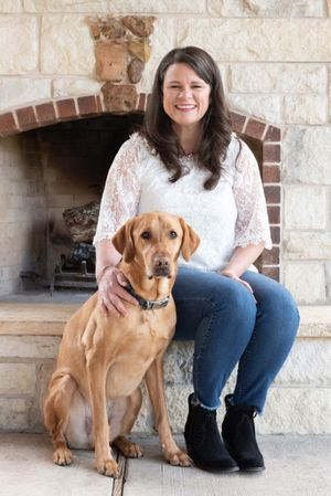 Woman and her dog sitting in front of fireplace