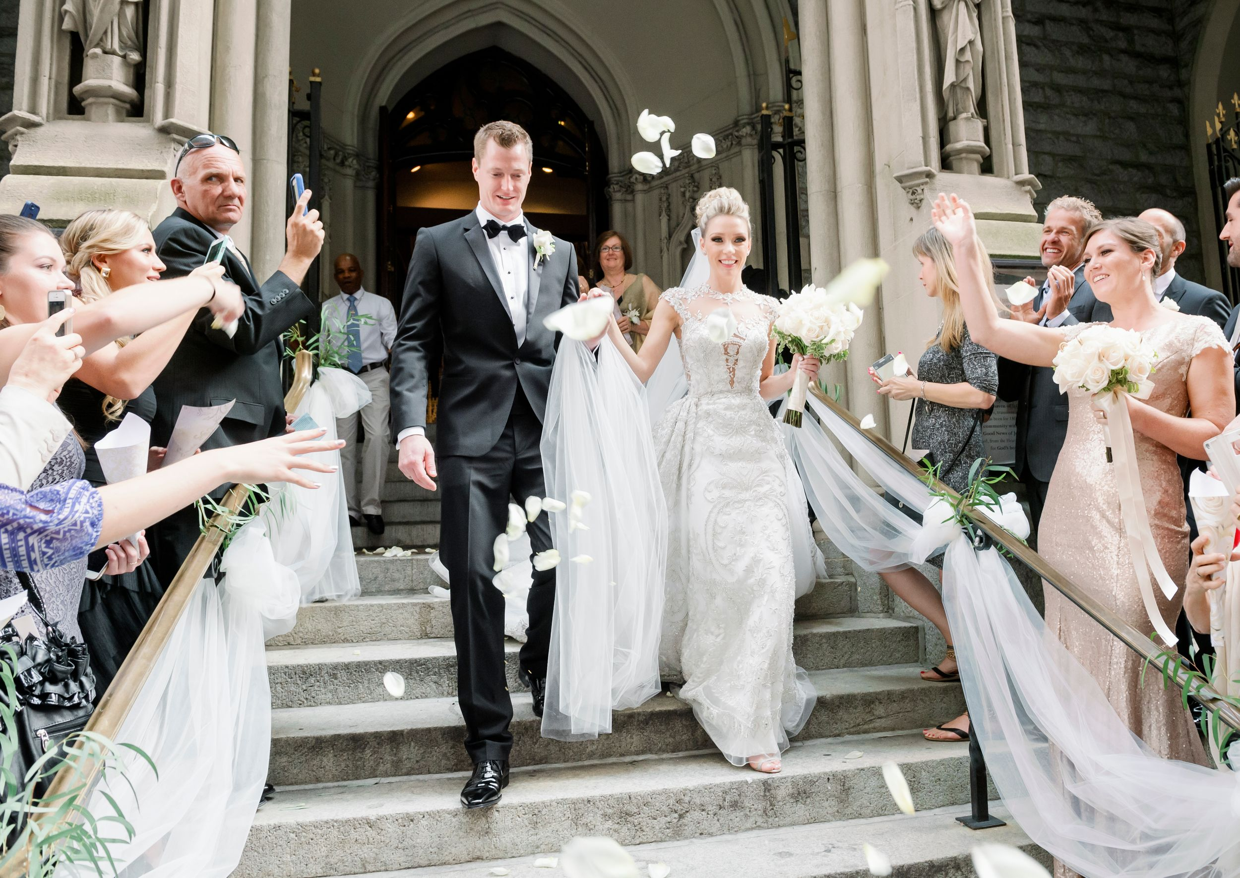 Candid wedding photograph of a bride and groom exiting a church in Philadelphia.