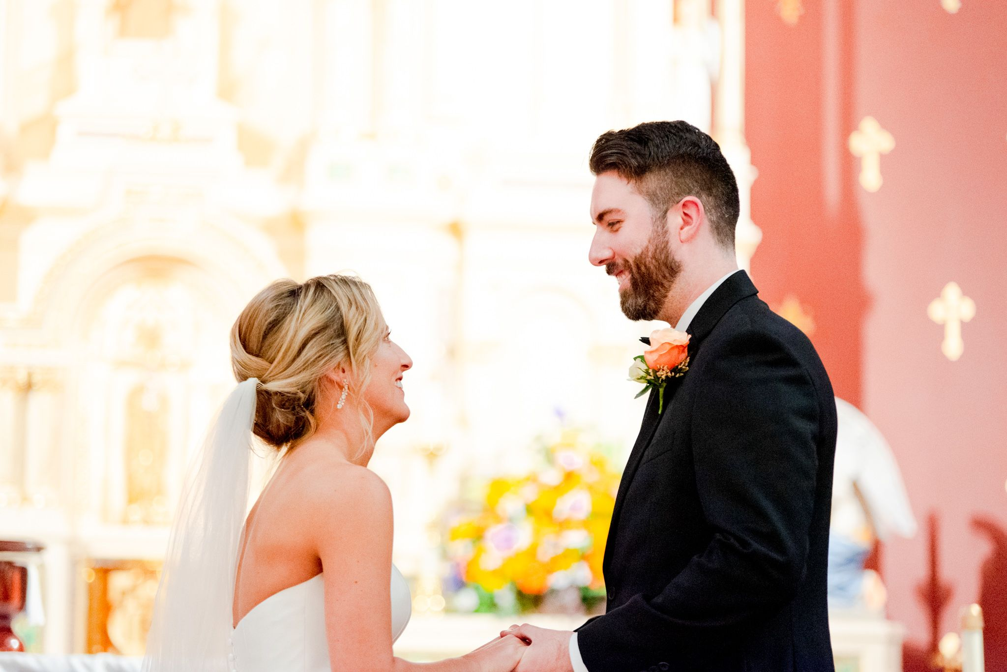 blonde bride with updo and veil smiling at her groom with brunette hair and beard in church