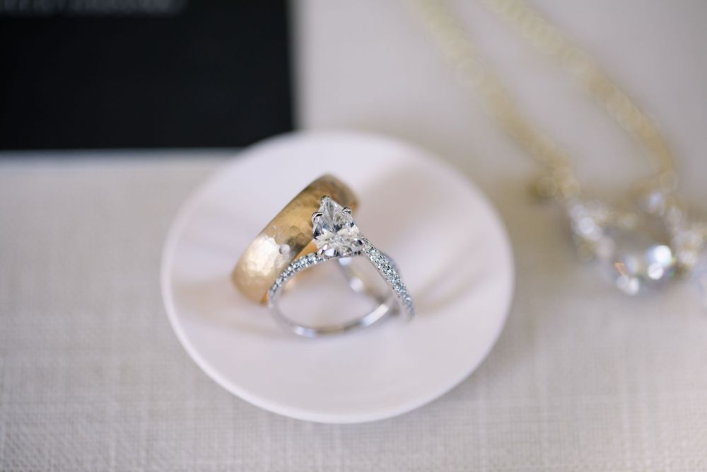 Bride and grooms' modern wedding rings sit in a ceramic dish.