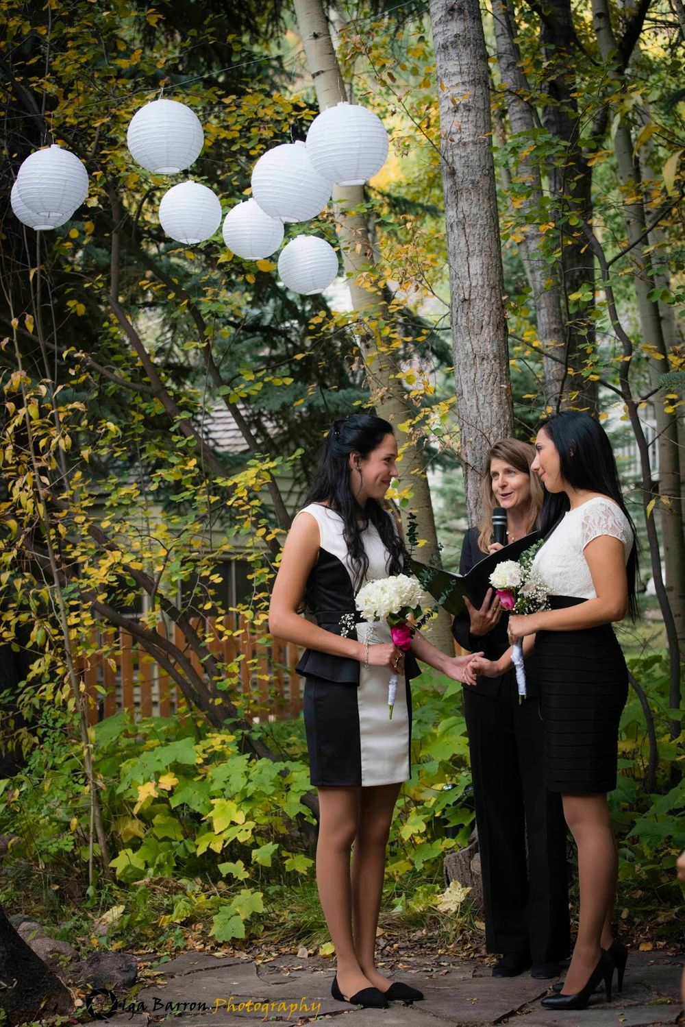 Two brides with officiant on a woodland dais