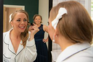 bride getting ready with bridesmaid looking in the mirror, Robert Nelson Wedding Photography
