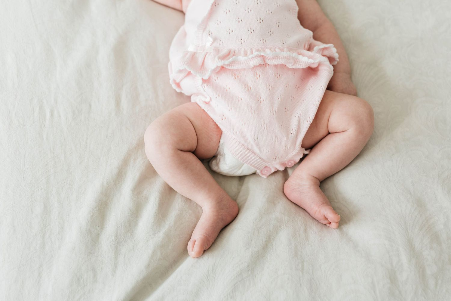 tiny bare newborn baby girl legs feet