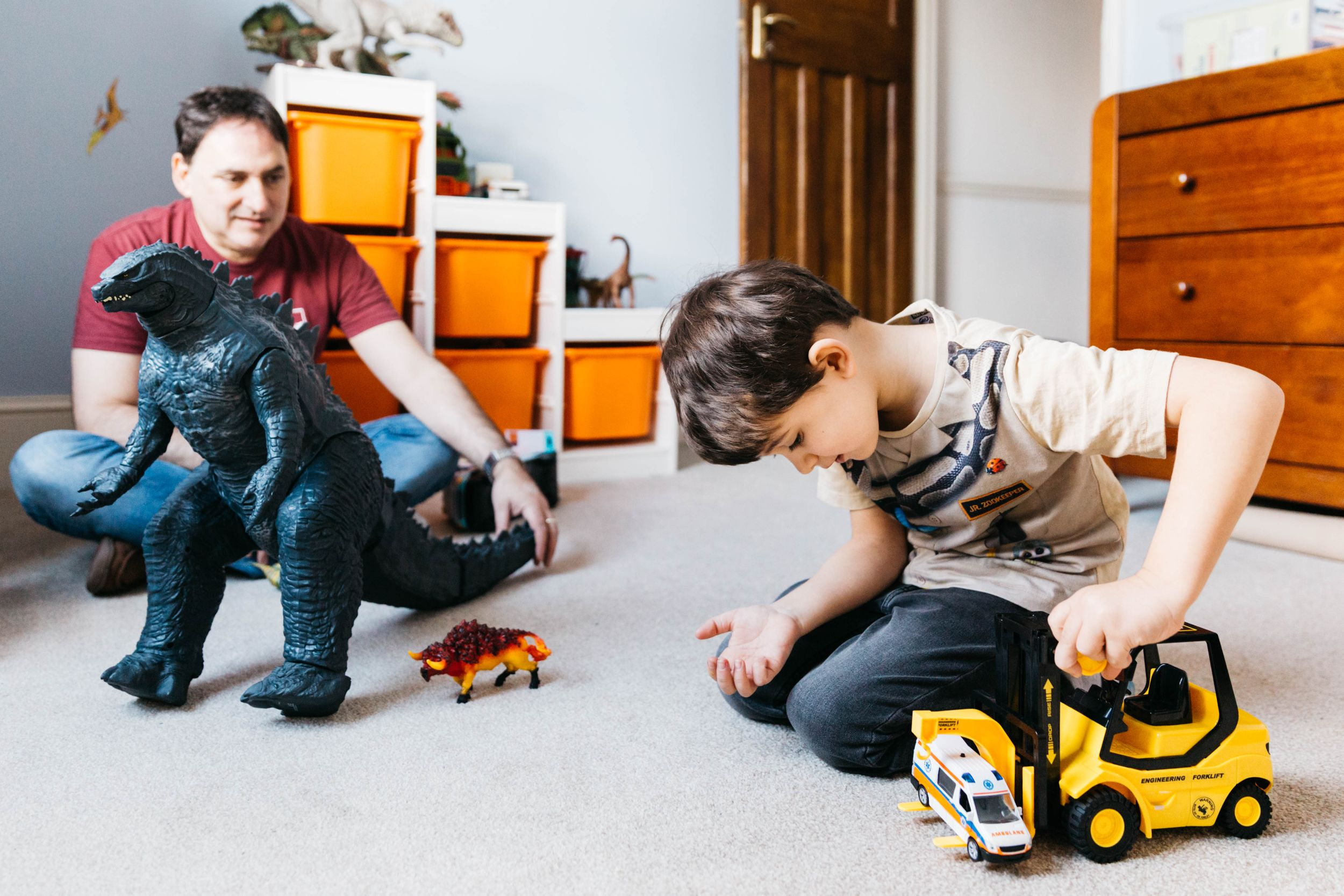 dad and son playing with dinosaurs cars in bedroom