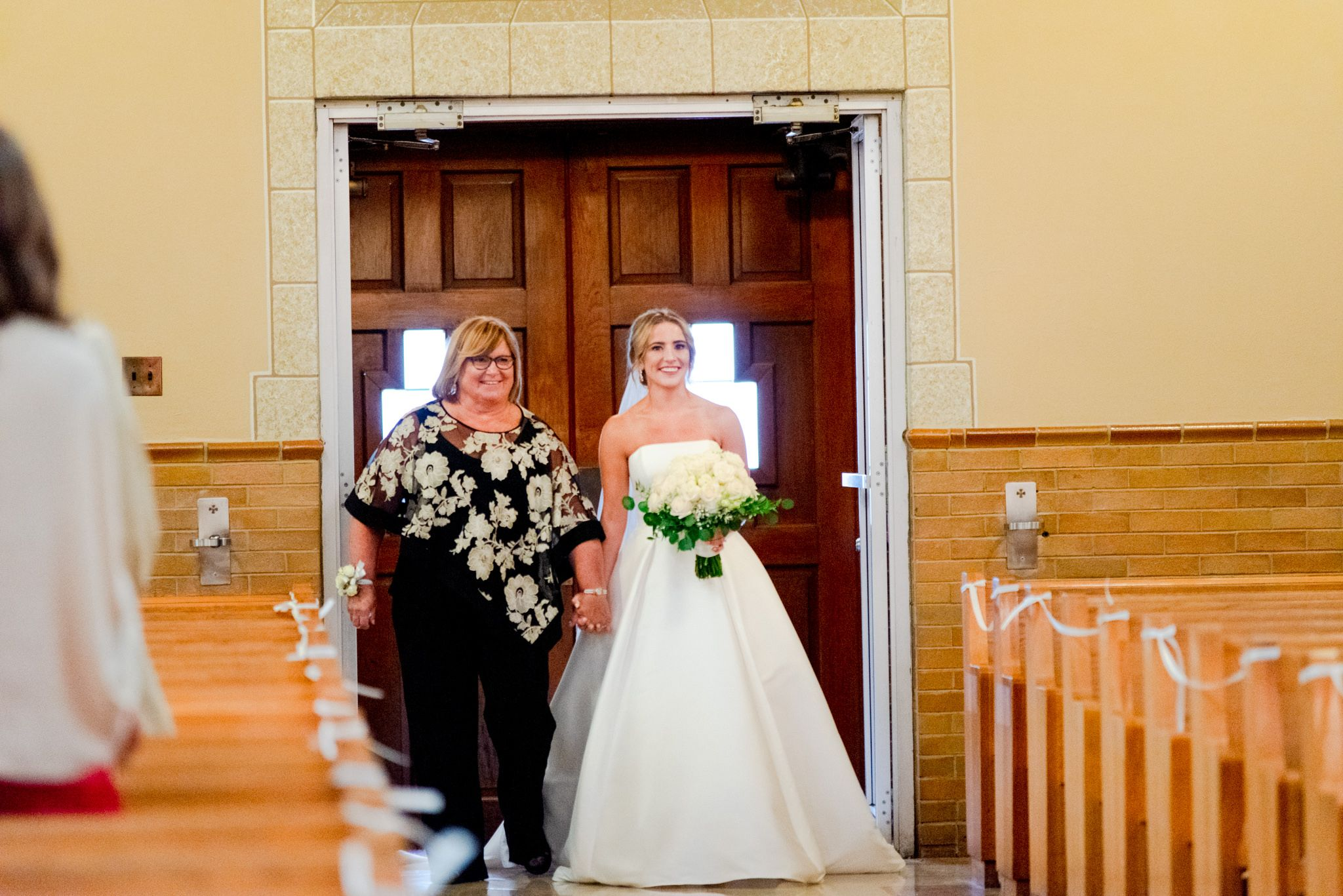 bride and mother of the bride walking down the aisle of the church both smiling and bride holding white bouquet