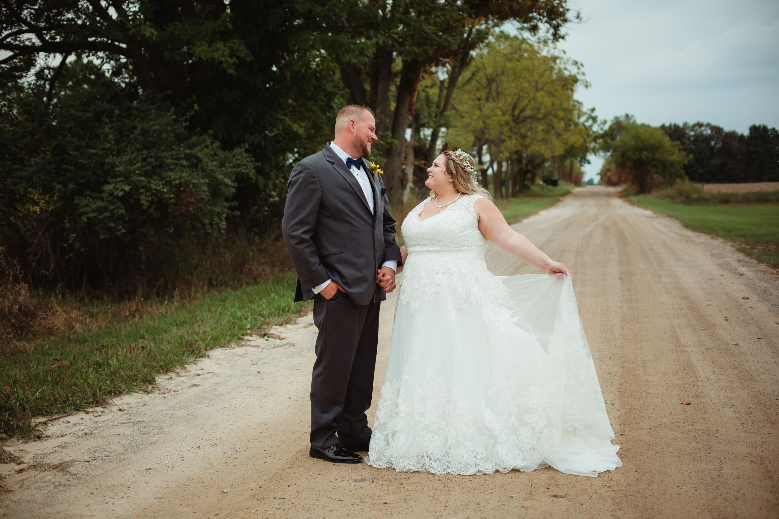 Bride and groom standing on a dirt road holding hands. The bride holds her dress out.