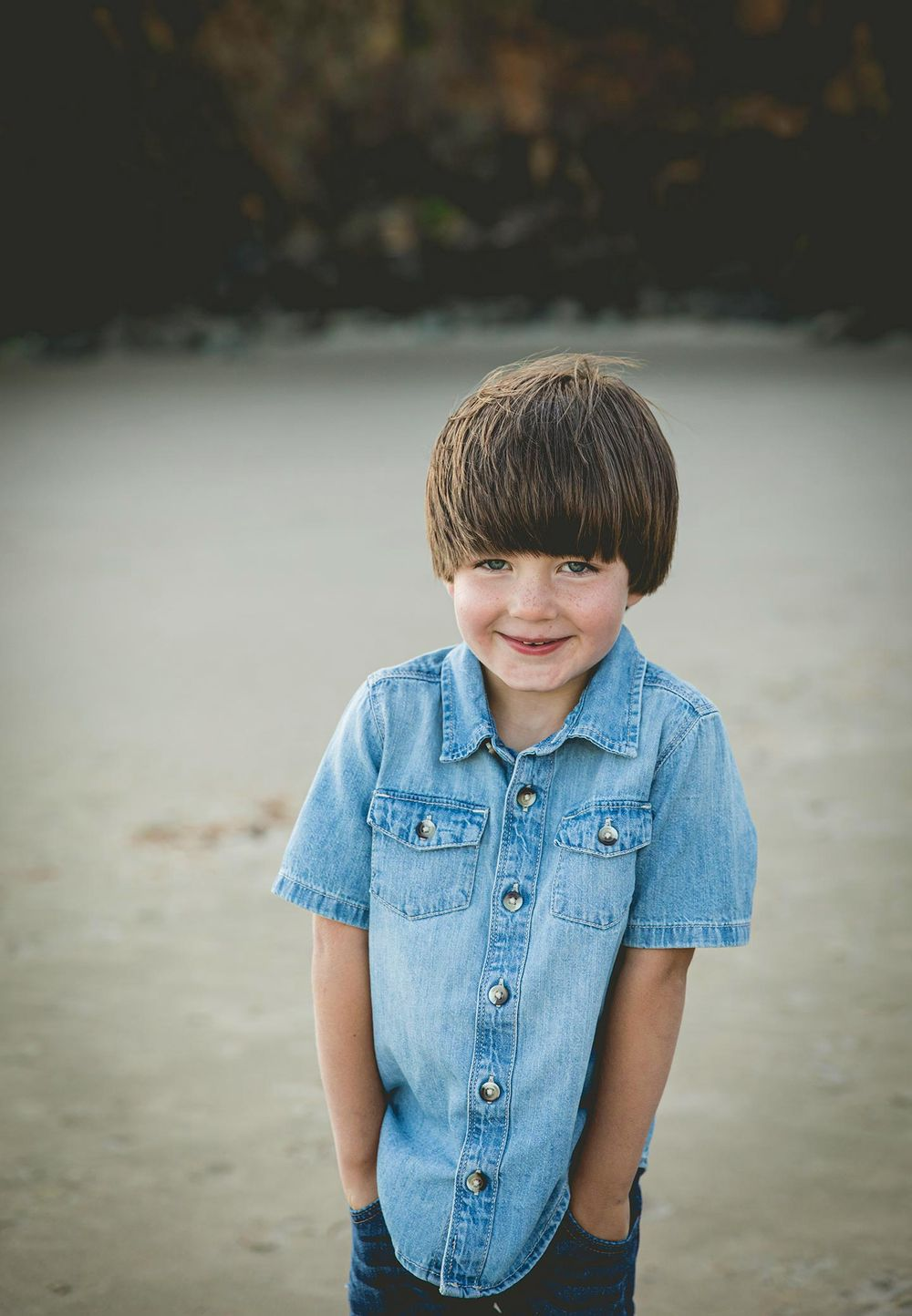 toddler boy wearing a denim button up shirt with his hands in his pockets on the beach