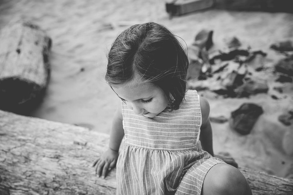 toddler girl sitting on driftwood at the beach