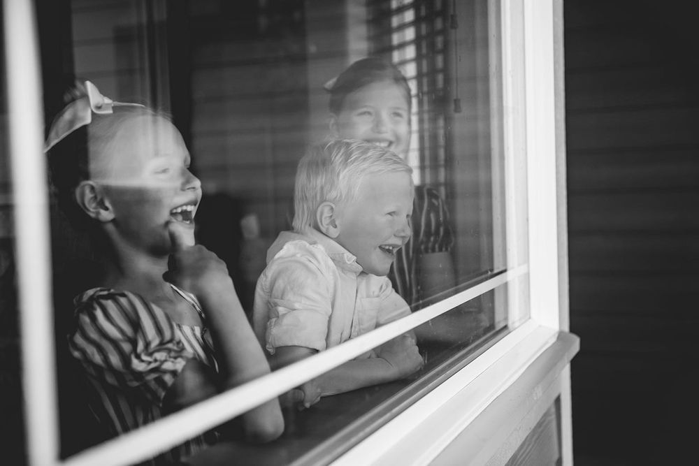 three siblings looking out their dining room window laughing