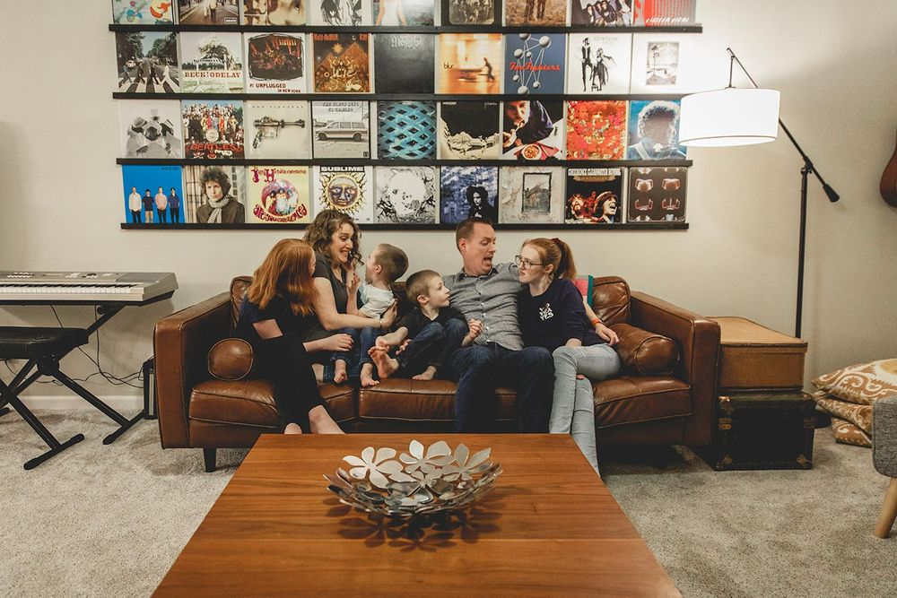 family of six sitting on their couch in their family room that has record albums hung on the wall