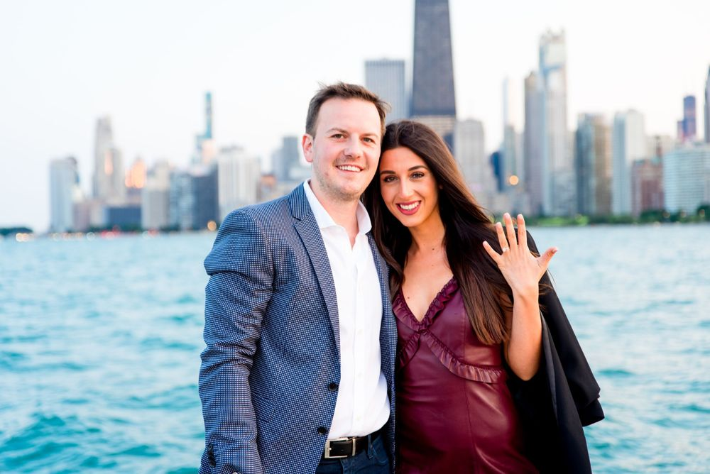 man and woman smiling together and woman holding up hand in front of skyline after Chicago Proposal
