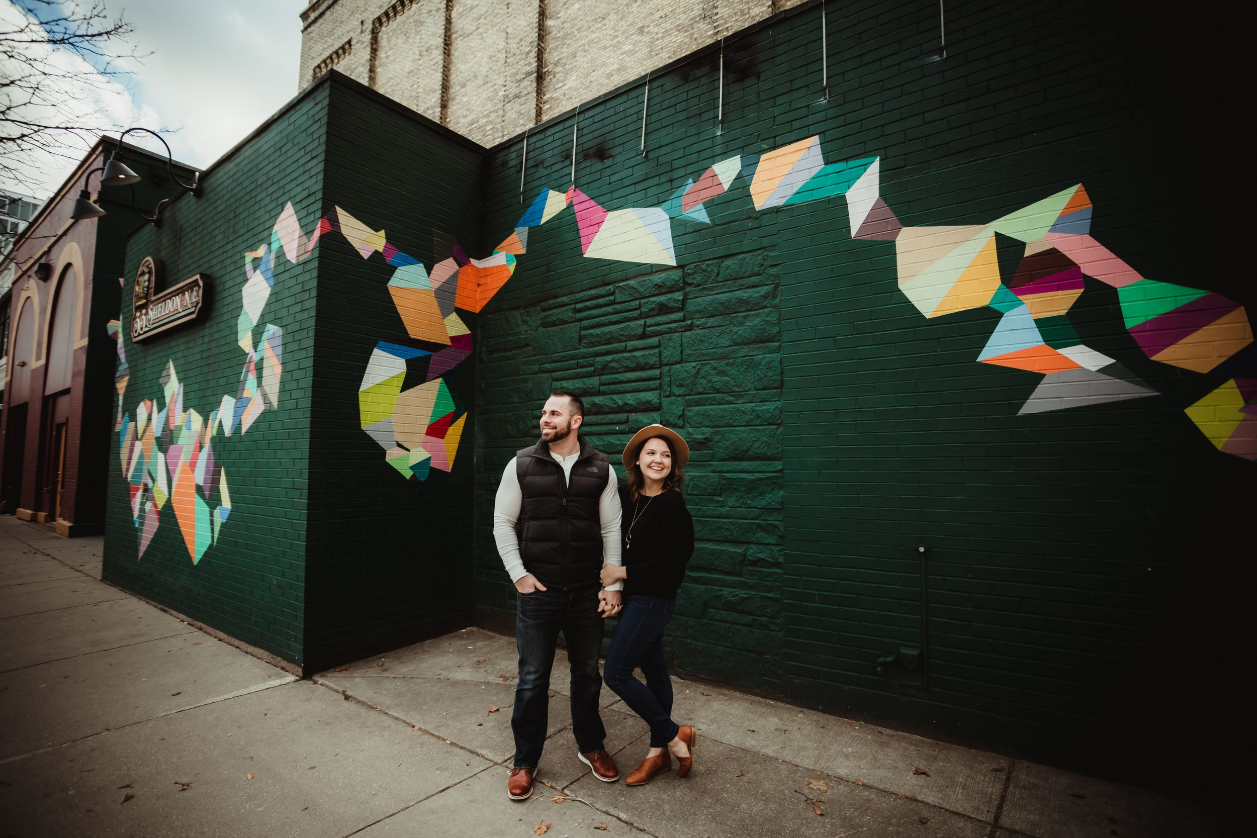 Man and woman hold hands and smile in front of a dark green wall with a colorful mural.